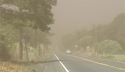 Dust clouds envelope passing cars on Highway 11