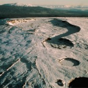Aerial photograph looking north-northeast across the summit area of Mauna Loa (elevation 4,169 meters or 13,679 feet). At the summit is Moku'äweoweo Caldera, a volcanic  depression 3 miles (5 kilometers) long.The pit craters in the foreground are part of the  upper southwest rift zone. Mauna Kea Volcano rises on the skyline.