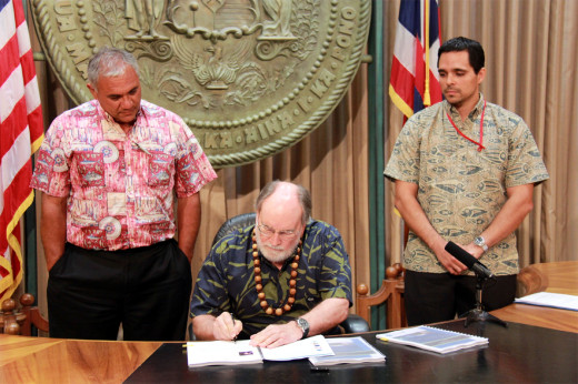 DLNR chair William Aila (left) and Office of Planning Director Jesse K. Souki (right) watch as Governor Neil Abercrombie signs the Hawaii Ocean Resources Management Plan