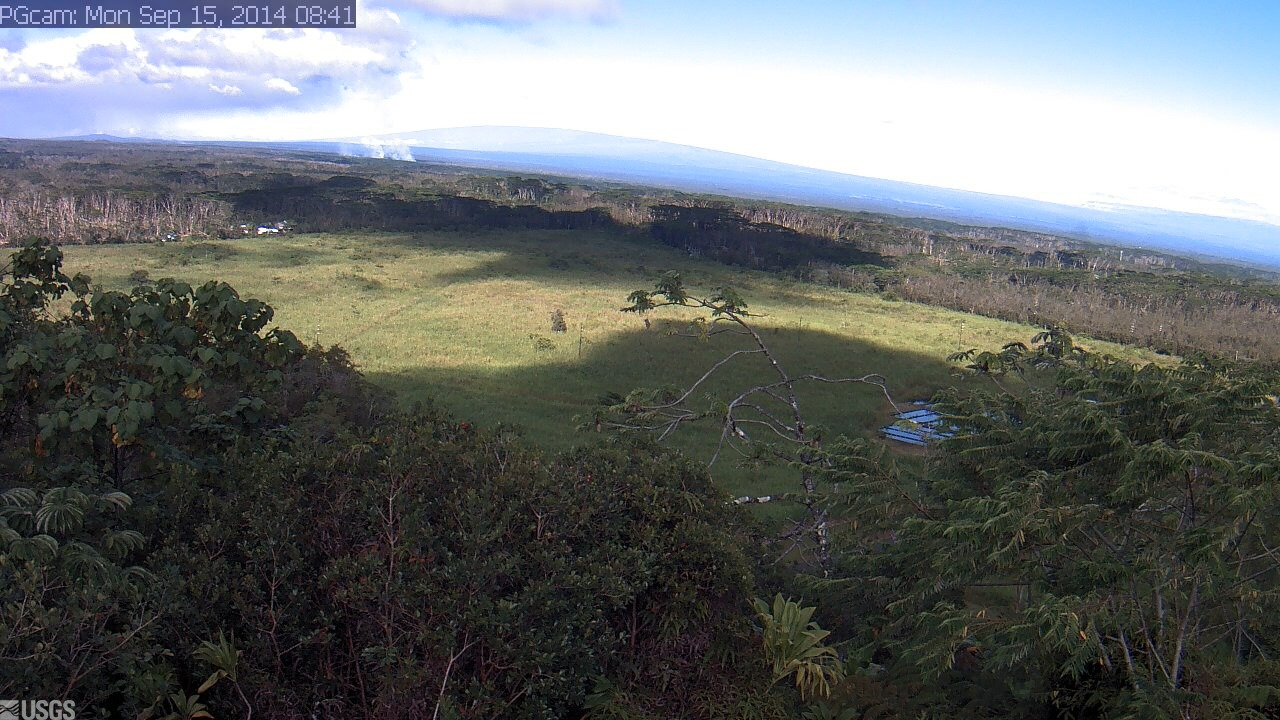 This USGS Hawaiian Volcano Observatory image is from a research camera positioned near Kapoho looking northwest. The advancing front of the June 27th lava flow is seen on the horizon, burning vegetation and sending smoke aloft in left center of the image.