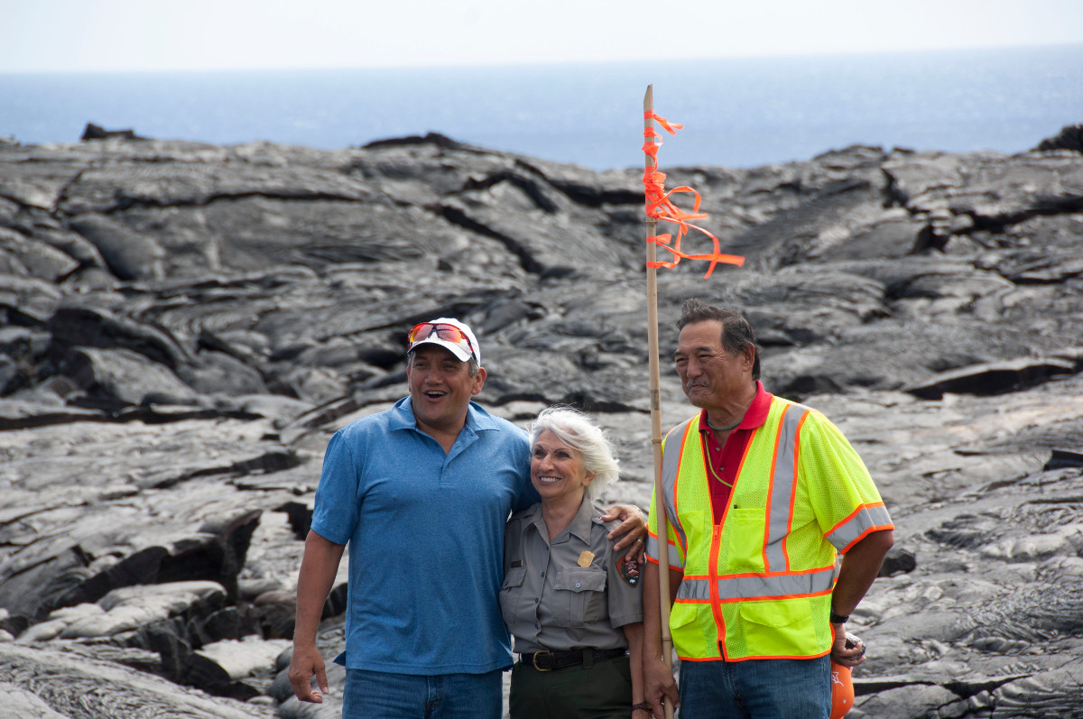 Mayor Billy Kenoi, County Public Works Director Warren Lee, and Hawaii Volcanoes National Park superintendent Cindy Orlando arm-in-arm in celebration, courtesy National Park Service