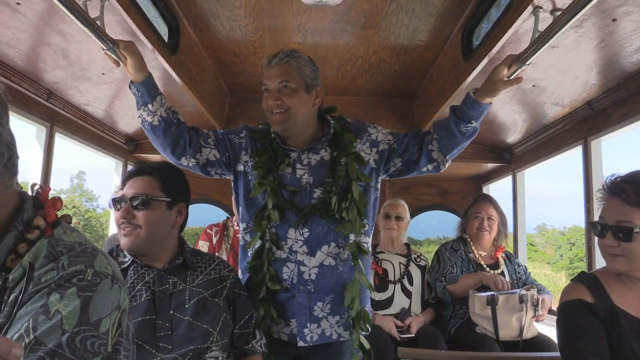 Mayor Kenoi smiles wide in the back of the trolley as it takes the first trip over the new bypass.