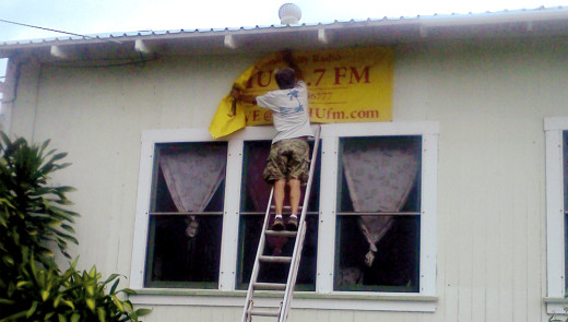 Mike McDonough, a local Pahala resident, assists in taking down the KAHU 91.7 FM station banner from the side of the building (June 2013, courest KAHU Radio)