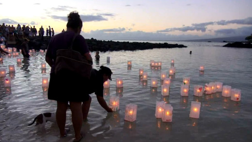 Lanterns let go, floating in the calm waters of the bay