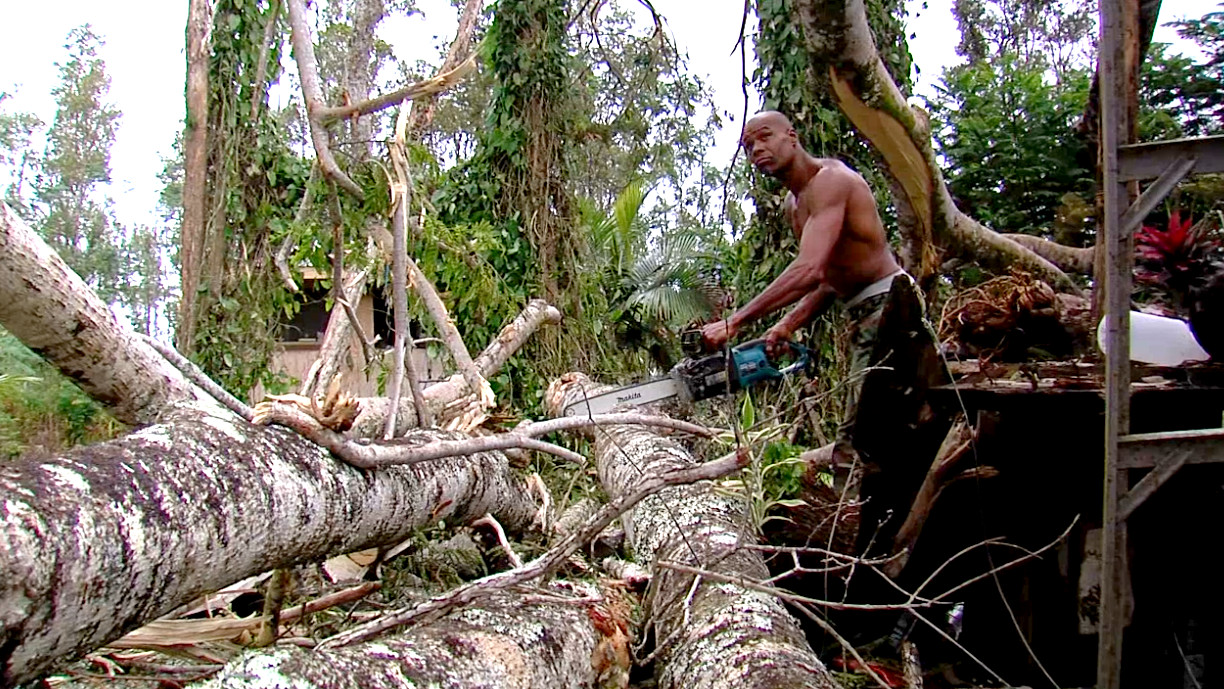 Ira, an artist and resident of Nanawale Estates, cuts his way out of a fallen albizia tree. The tree crushed his studio area outside his home.