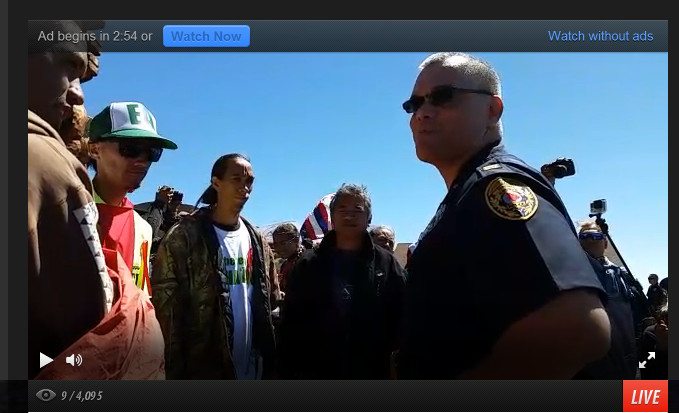 Police speak to TMT opponents blocking the road.  Image from live video streamed from the scene by Kerri Marks with Occupy Hilo