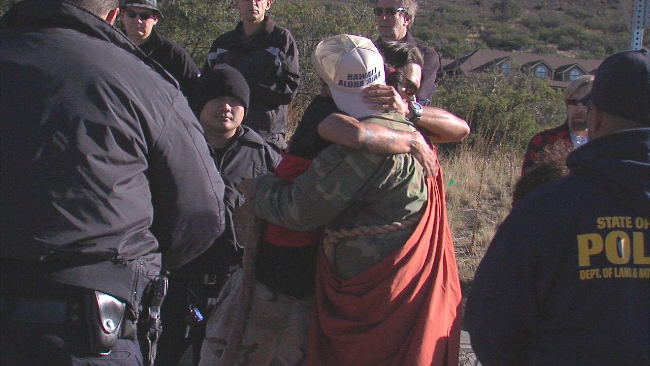 Kahookahi Kanuha of Kailua-Kona hugs a friend before being handcuffed Thursday on Mauna Kea.