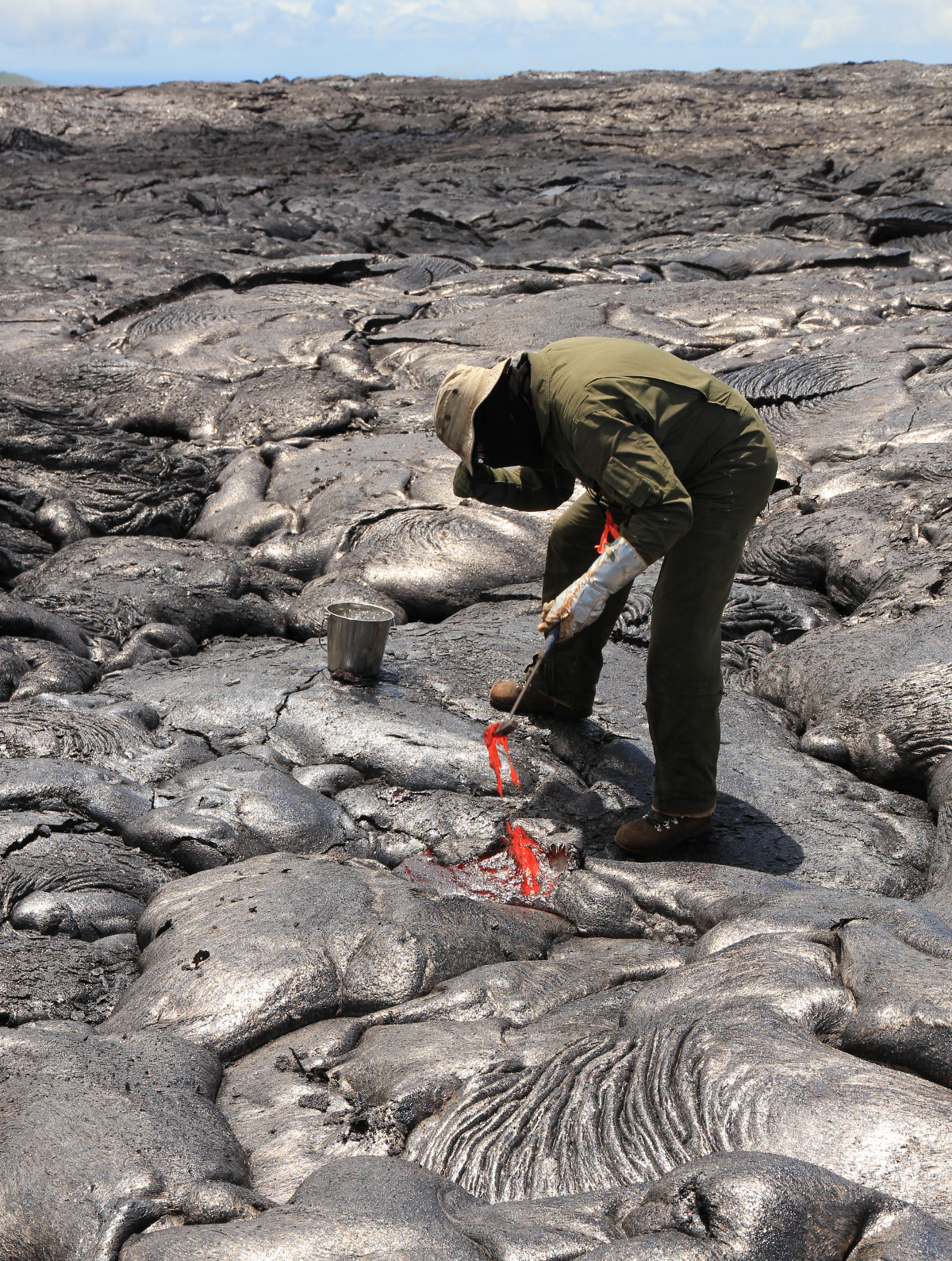 An HVO geologist collects a sample of lava for chemical analysis, quenching it in a bucket of water. (USGS)