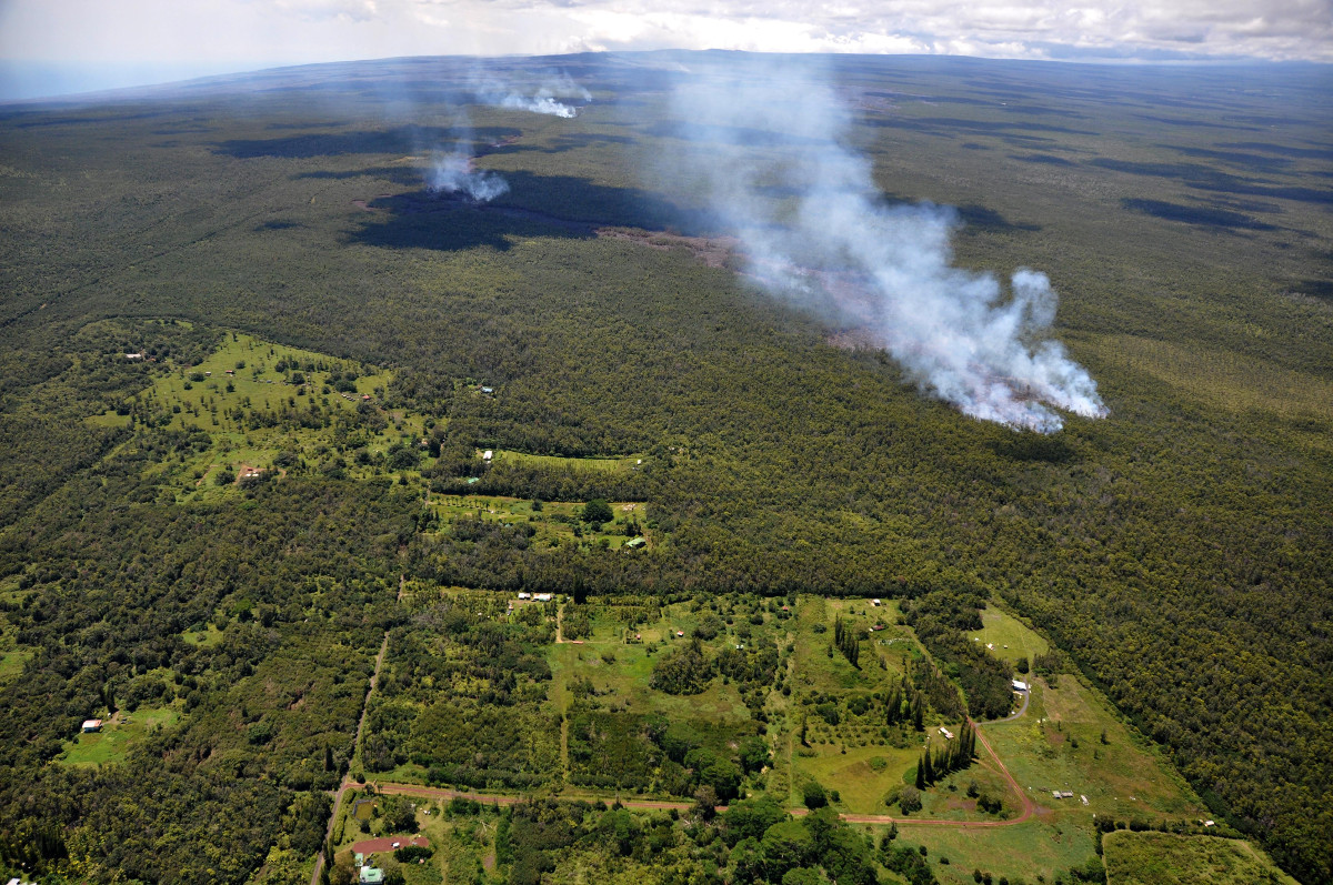 From September 4, 2014, to March 25, 2015, USGS Hawaiian Volcano Observatory scientists raised the Volcano Alert Level for Kīlauea from WATCH to WARNING as the June 27th lava flow advanced toward Pāhoa and posed an imminent hazard and threat to nearby communities and infrastructure.  Shown here on September 12, the leading edge of the lava flow (marked by dense smoke, middle right) burned through thick forest less than 200 m (220 yds) from the boundary of Kahoe Homesteads (lower left).  USGS photo.