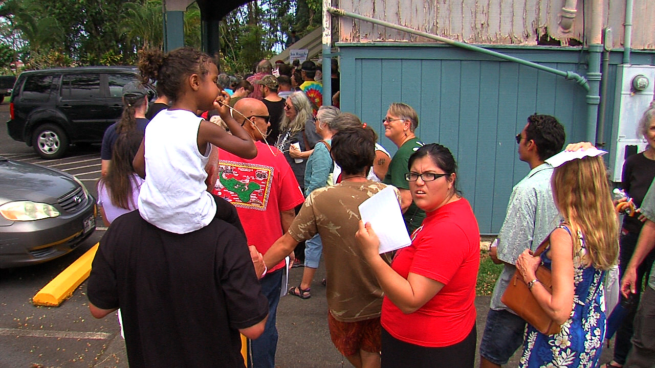People inch forward in a line that stretched around the Keaau Community Center.
