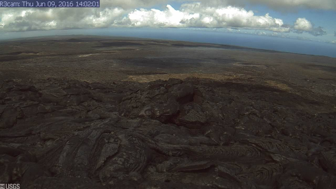 This USGS image is from a research camera positioned on the southeast flank of Puʻu ʻŌʻō, looking toward the active flow advancing to the southeast. The breakout point is at the left edge of the image, and the mid-field skyline at the right is roughly coincident with the top of the pali. See it live here.