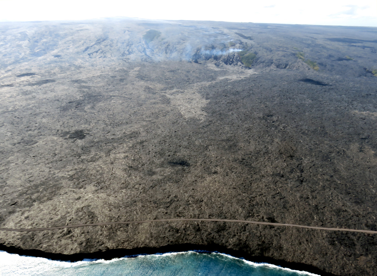(USGS photo) The position of the lava flow front relative to the shoreline can be seen in this aerial photograph. The leading edge of the flow, which was 1.1 km (0.7 miles) from the ocean today, is the light-colored area near the center of the image. More vigorous breakouts were active upslope, near the base of the pali. Fume from the lava tubes and smoke from burning vegetation are visible on the pali in the upper part of the photo. Puʻu ʻŌʻō is visible on the upper left skyline.