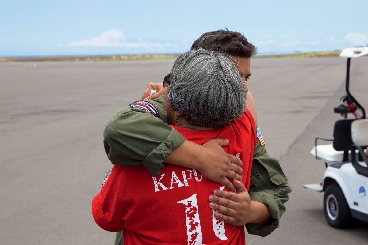 The mother of Sidney Uemoto hugs Coast Guard crews following her daughter's rescue.  (U.S. Coast Guard photo by Lt. Cmdr. Kevin Cooper/Released)