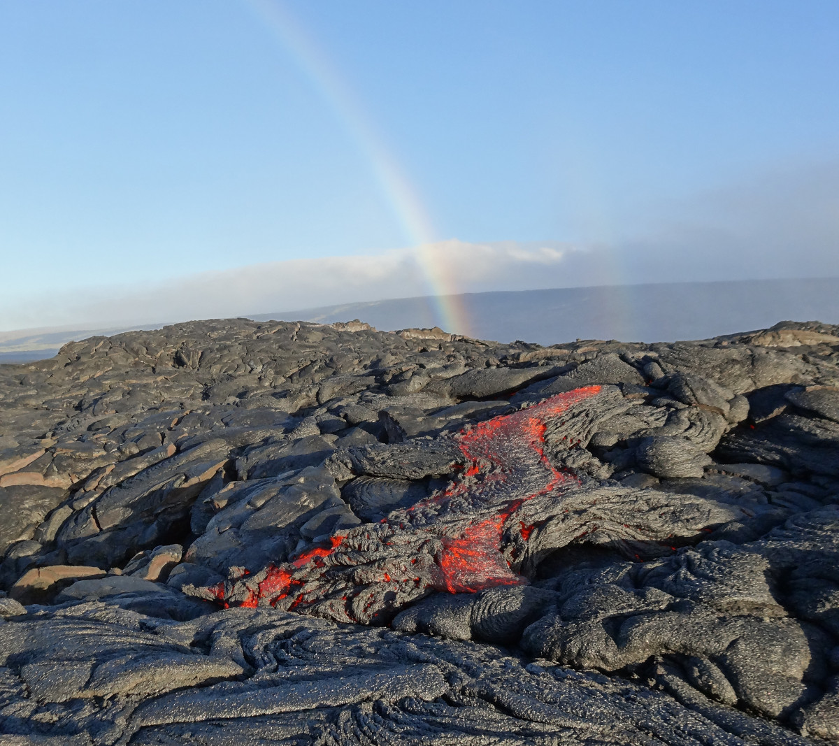 (USGS photo) A faint double rainbow provided a beautiful backdrop for sluggish pāhoehoe lava oozing out from near the flow front on the morning of July 22.