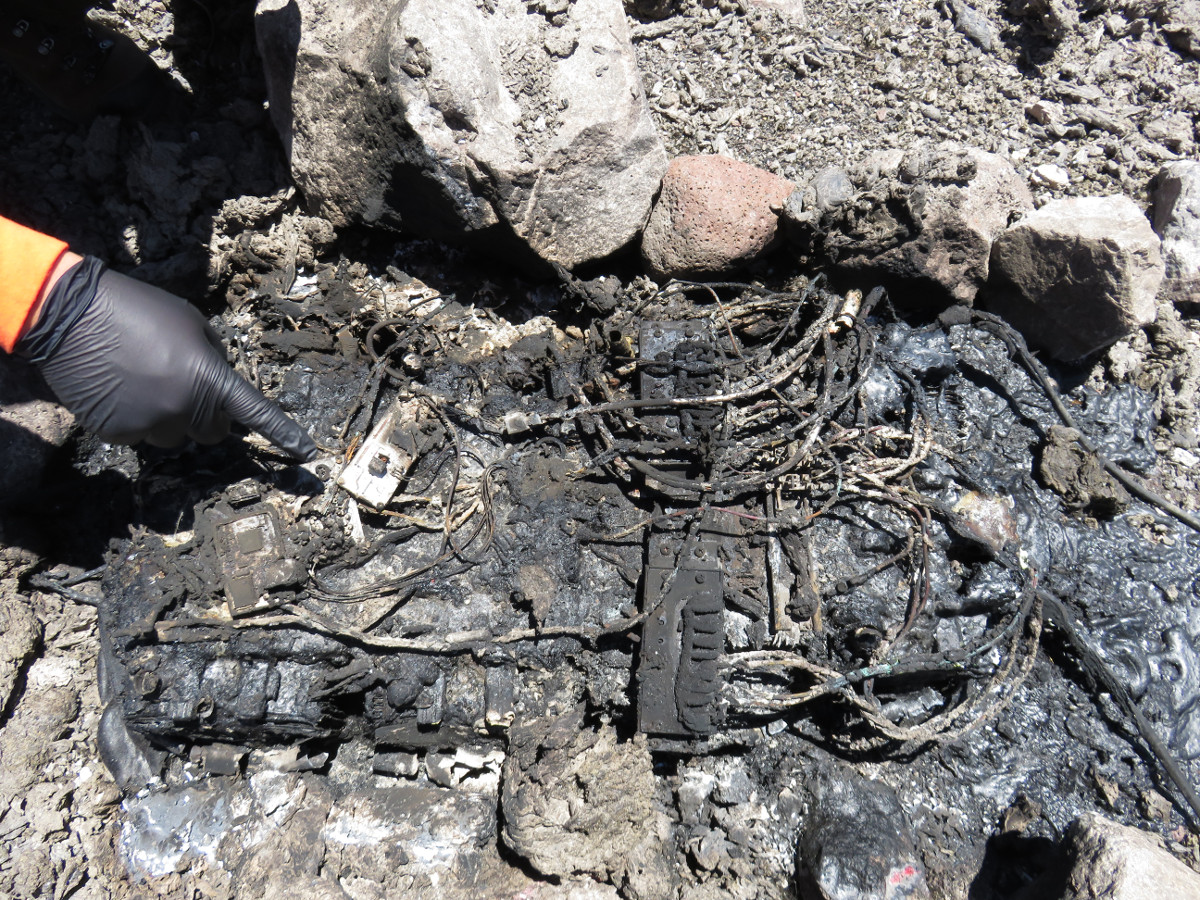 (USGS photo) This pile of charred wires and metal components, surrounded by melted plastic, is all that remains of the power supply for one of HVO's gravity instruments located about 24 m (80 ft) from the crater rim.