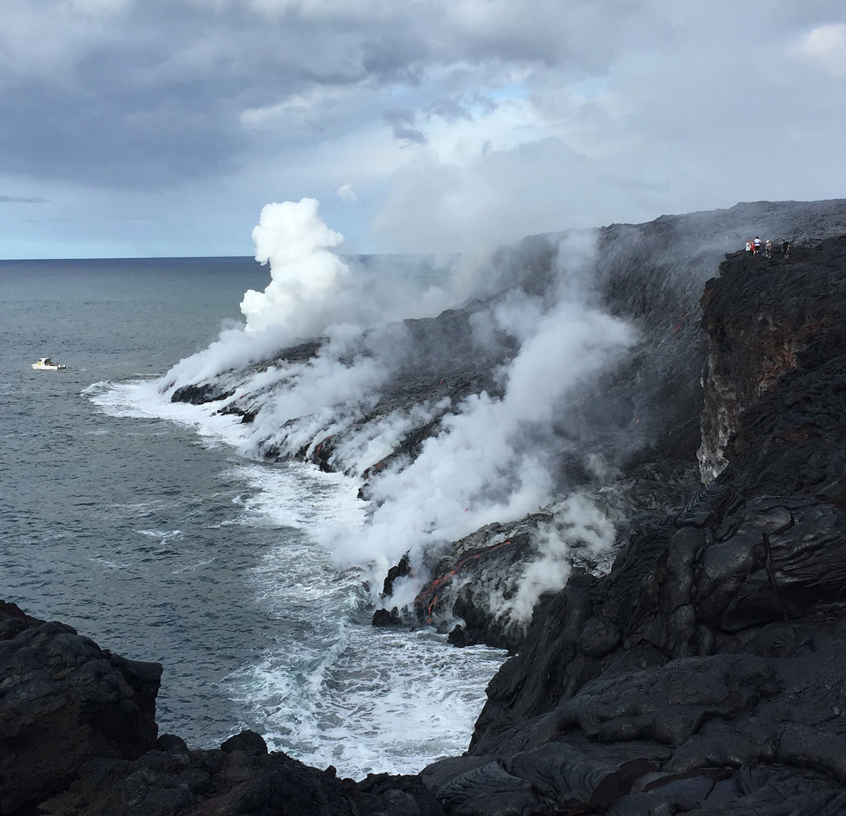 (USGS photo) The white plume formed by the interaction of lava and seawater is a corrosive mixture of super-heated steam, hydrochloric acid, and tiny particles of volcanic glass, all of which should be avoided. Lava deltas (new land formed at the ocean entry) can collapse without warning. Should the lava delta shown here collapse, fragments of molten lava and blocks of hot rock would be thrown both inland and seaward, potentially impacting people on the cliff above the ocean entry and in the boat in front of the delta, scientists say.