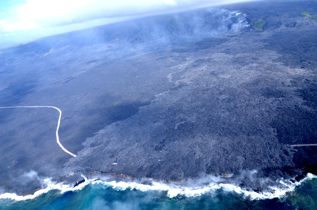 (USGS photo) Aerial view of the Kamokuna ocean entry and the Emergency Access Road cut by the 61g lava flow. 61g lavas are lighter in color than older lavas on the coastal plain. Upslope, a trail of fume marks the lava tube as it passes over the pali.