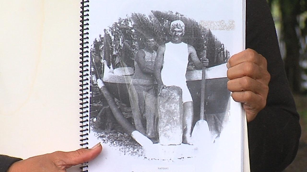 George Kahilihiwa Kekaula and his son-inlaw David Napeahi stand with the stone, Makaoku'i Ka Lani, in this ca. 1920 photo by Theodore Kelsey.