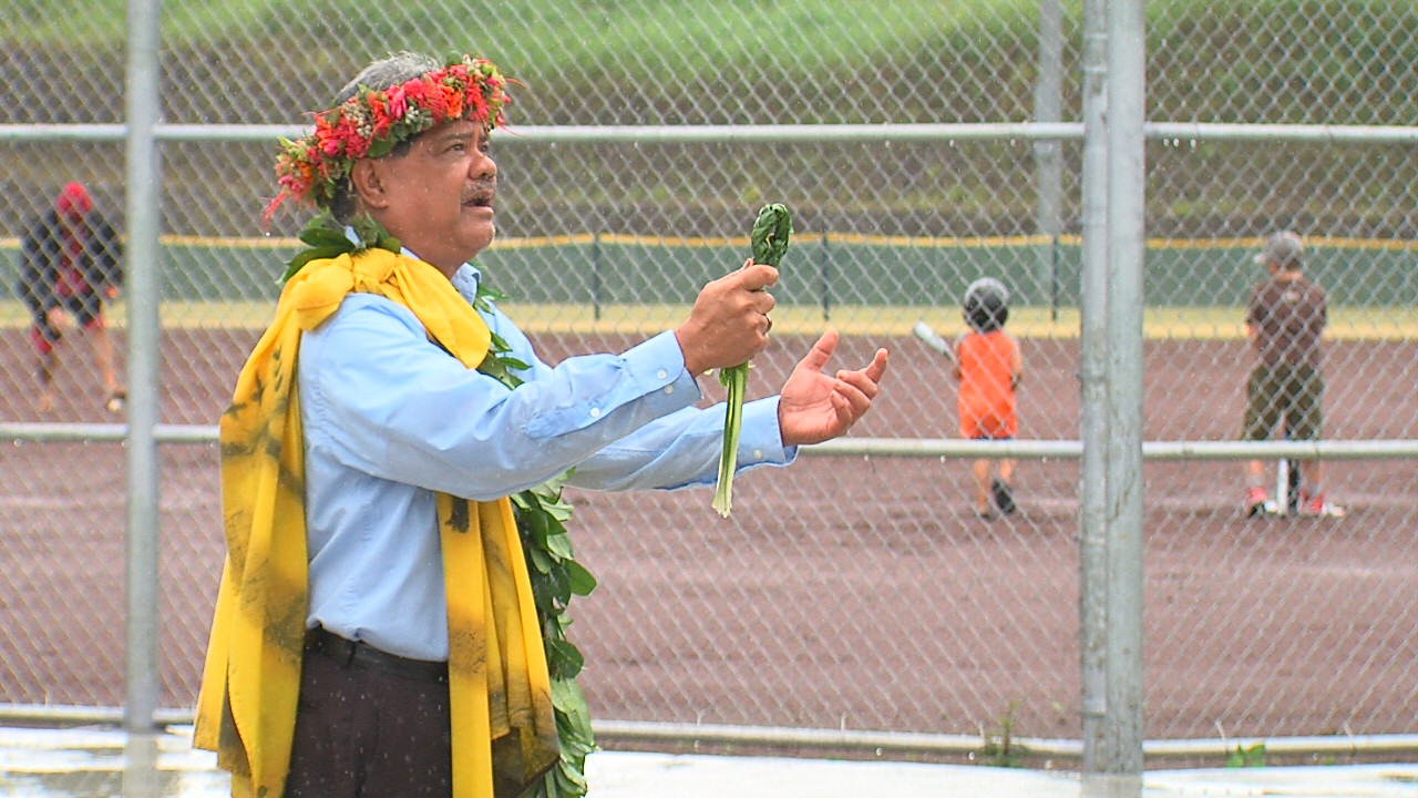 Standing in the rain, Kumu Crabbe blesses the new facilities in Pahoa, while a family plays on the baseball field behind him.
