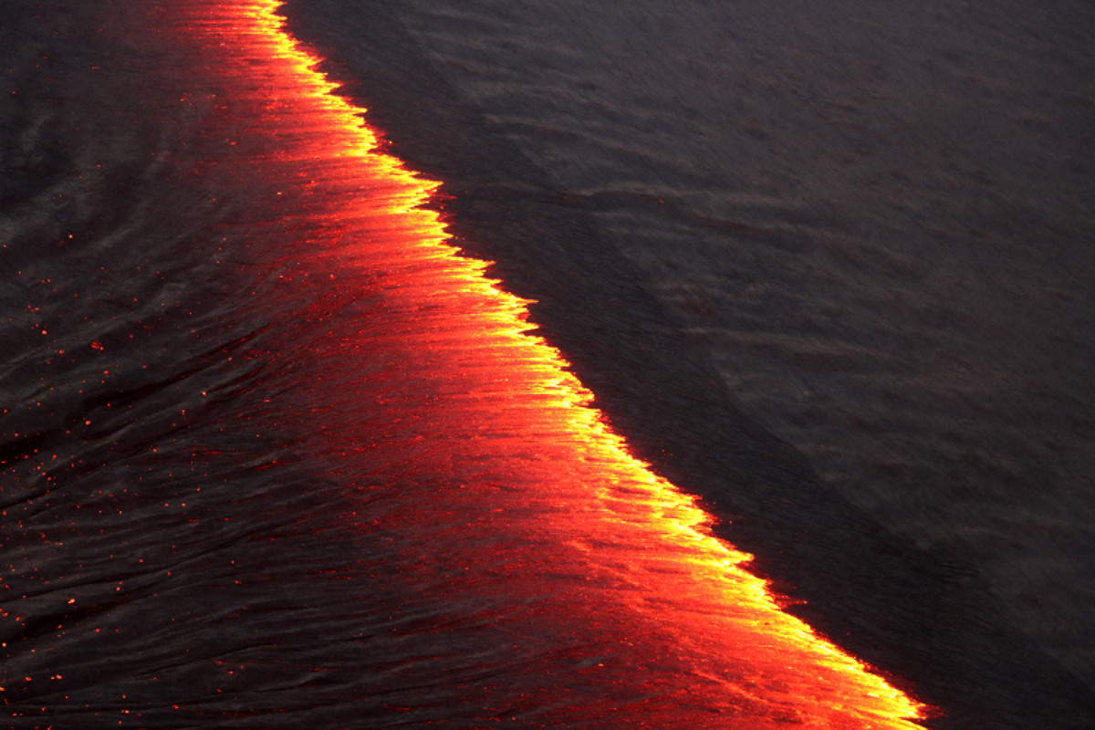 On the lava lake, the crustal plates on both sides of the incandescent line are migrating to the south, but the crust on the left side is moving more rapidly to the south than the crust on the right. As the semi-solid crust pulls apart, molten lava upwells between the two plates to create new crust. (USGS photo)